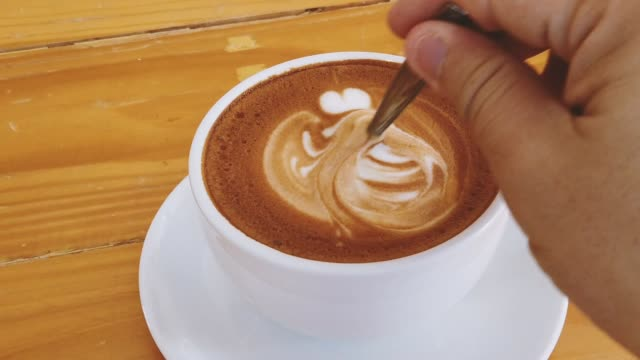hot coffee latte art stirring slow motion close-up - coffee variation stock videos & royalty-free footage