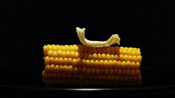 Hot corn. Slice of butter melting on sweetcorn cob. Timelapse.
