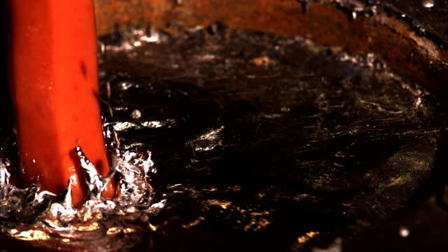 vídeos de stock, filmes e b-roll de a hot dog breaches the surface of a bowl of mercury and begins smoking as the metal boils. - mercúrio metal