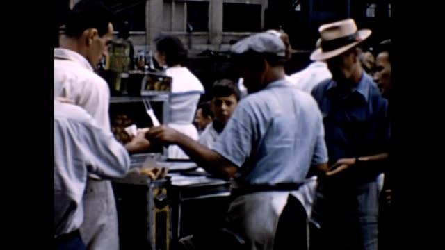 vídeos de stock e filmes b-roll de 1957 hot dog vendor and dock workers - hot dog