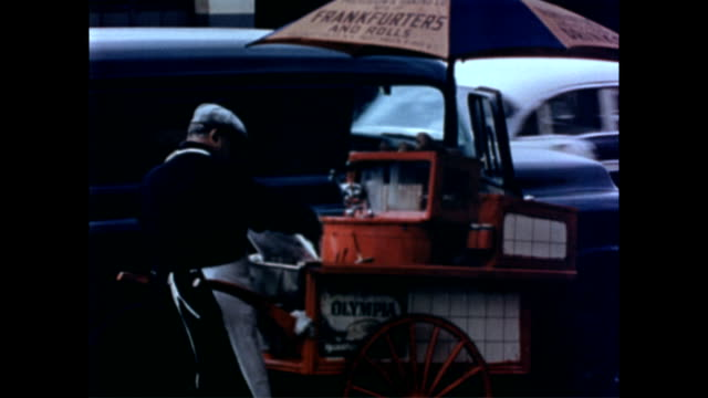 hot dog vendor cart parked outside on the sidewalk / vendor holding hot dog and bun in one hand and scooping topping with the other / man eating hot... - anno 1958 video stock e b–roll