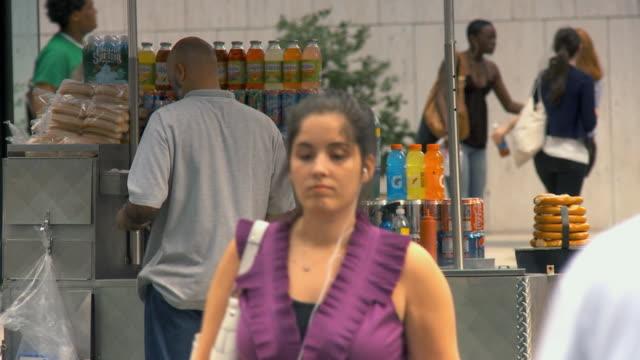 vídeos de stock e filmes b-roll de ms hot dog vendor on busy street, people walking by / new york city, usa - feirante