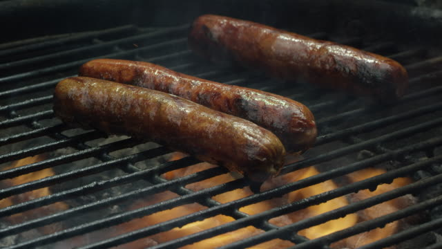 hot dogs sizzle and cook on a flaming grill - grigliare video stock e b–roll
