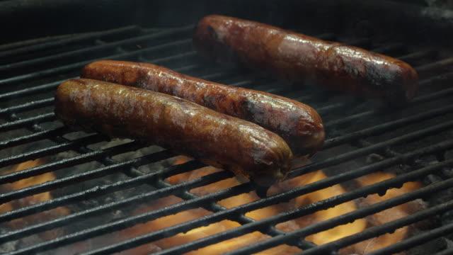 Hot Dogs brutzeln und Kochen auf einem brennenden Grill