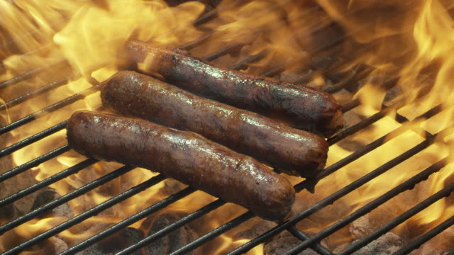 hot dogs sizzle and cook on a flaming grill - juicy stock videos & royalty-free footage