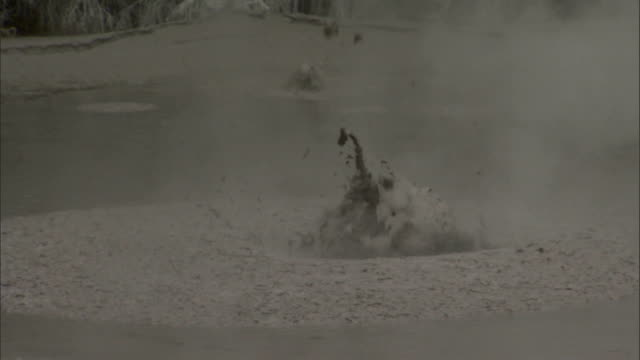 Hot ground water causes mud and clay to bubble to the surface of a thermal pool. Available in HD.
