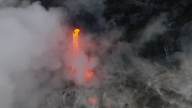 Hot lava flow with Pacific ocean waves in Hawaii Volcanoes National Park.