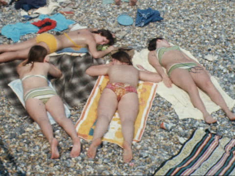 brighton beach during heatwave; england: east sussex: brighton: mass people on beach couple oil each other people on shingle in bikini lying group... - swimwear stock videos & royalty-free footage