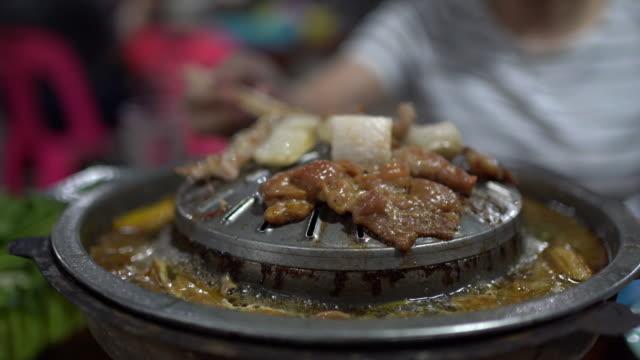 heißes fleisch barbecue auf grillpfanne. koreanischer barbecue im thailändischen stil mit schweinegrill und gemüse auf der heißen pfanne. - kalbfleisch stock-videos und b-roll-filmmaterial