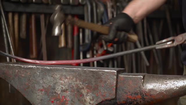 vídeos de stock e filmes b-roll de hot metal bar hit with hammer on anvil - ferro metal