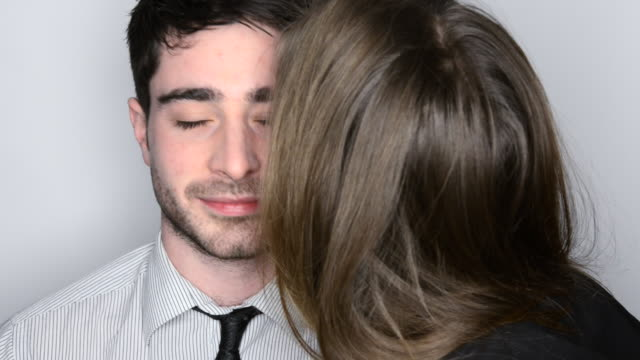 stockvideo's en b-roll-footage met cu hot of man being kissed on cheek by woman wearing lipstick / london, greater london, united kingdom - schaamte