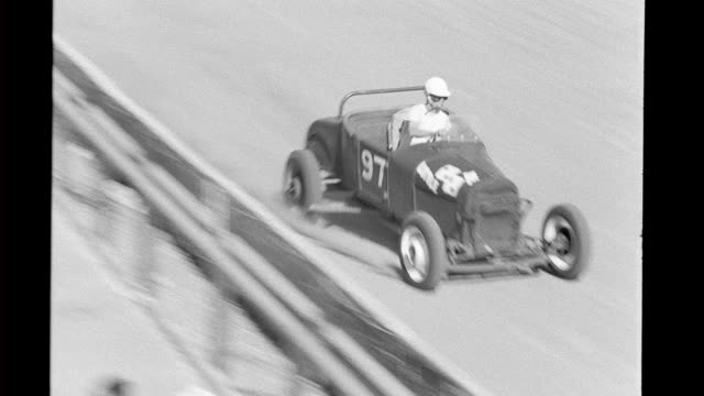 vídeos de stock, filmes e b-roll de hot rods rounding track racing / crowd in stands*** hot rods and their drivers on january 01 1940 in california - hot rod