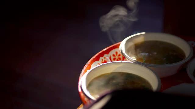朝のトレイの紙のボウルに熱いスープ - トウガラシ類点の映像素材/bロール