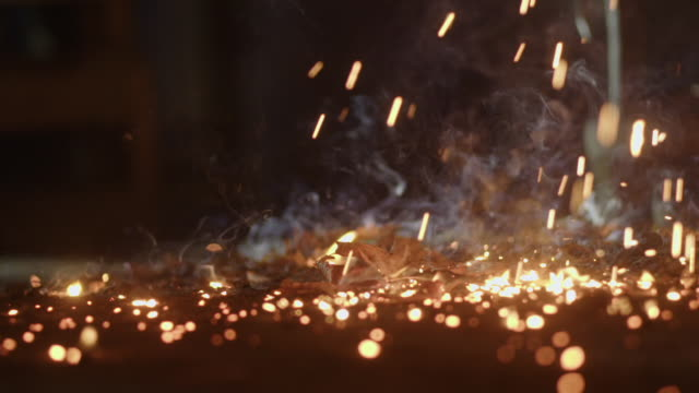 Hot sparks drop to the floor of a blacksmithing workshop.