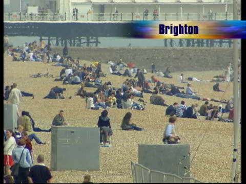 hot spell leading up to easter; itn england: yorkshire: scarborough: ext cms little girl petting donkeys on the beach gv crowded beach gv people... - 英国スカーブラ点の映像素材/bロール