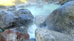 Hot spring sources water flowing pass though the way and rocks running down the valley in a warm stream in Kusatsu Onsen hot spring, Japan