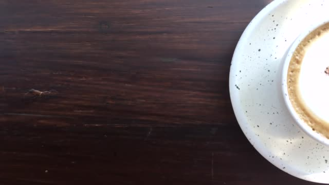 hot steaming cup of coffee standing on a wooden table