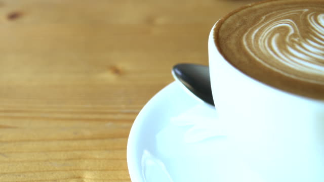 hot steaming cup of coffee standing on a wooden table - coffee drink stock videos & royalty-free footage