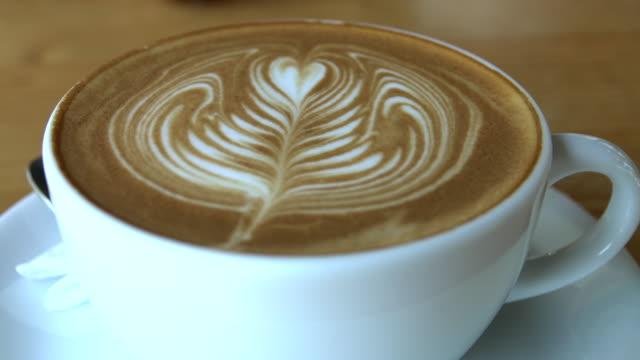 木製のテーブルの上に立つコーヒーの熱い蒸しカップ - カプチーノ点の映像素材/bロール