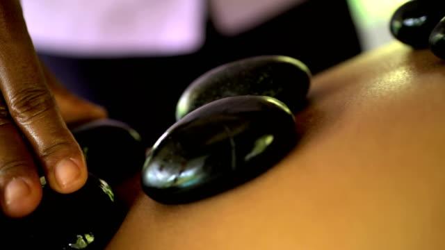 hot stone massage on young asian female bali - spa treatment点の映像素材/bロール