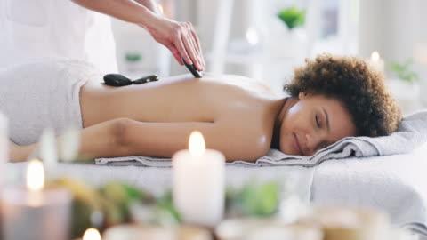 eine hot-stone-massage fördert die tiefenentspannung - live ereignis stock-videos und b-roll-filmmaterial
