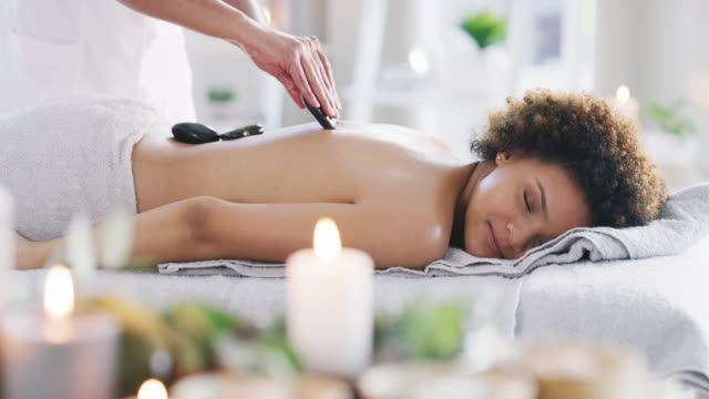 stockvideo's en b-roll-footage met een hot stone massage bevordert diepe ontspanning - spa treatment