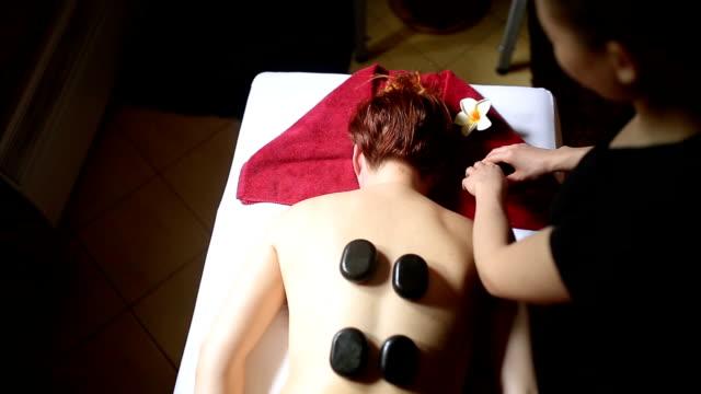 vídeos de stock, filmes e b-roll de a massagem com pedras quentes - lastone therapy