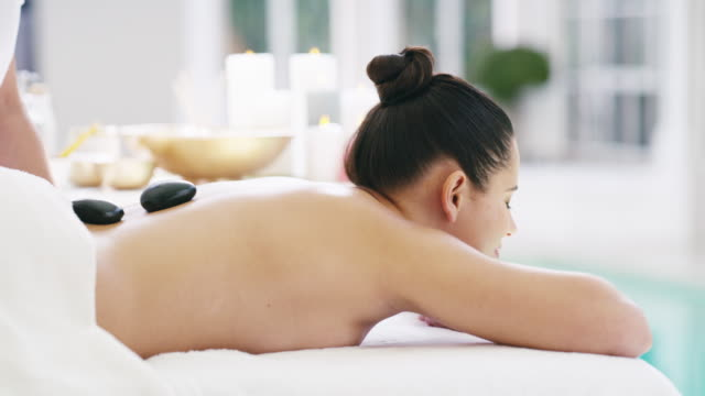 hot stone therapy acts as a natural painkiller - lastone therapy stock videos and b-roll footage