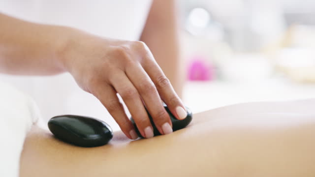 hot stone therapy increases flexibility in joints - spa treatment stock videos & royalty-free footage