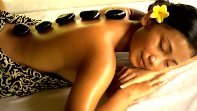 hot stone treatment on asian female client bali - spa treatment点の映像素材/bロール