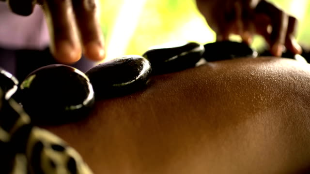 hot stone treatment on young asian female bali - spa treatment点の映像素材/bロール