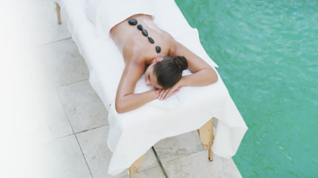 hot stones help promote deep relaxation - masseur stock videos & royalty-free footage
