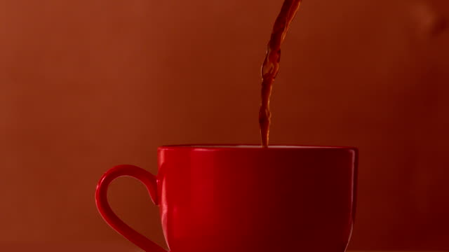 hot tea and milk pouring into red cup - svart te bildbanksvideor och videomaterial från bakom kulisserna