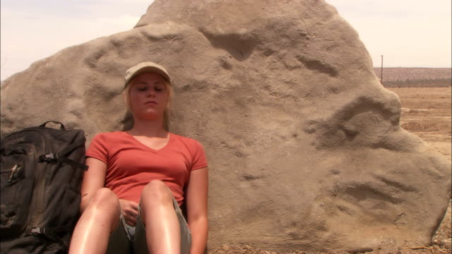 vidéos et rushes de a hot, tired woman leans against a desert boulder. - fragilité