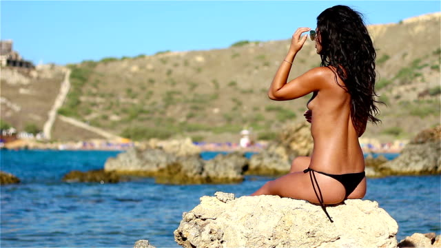 hot topless girl enjoying on rock by the sea - little girls flashing stock videos and b-roll footage