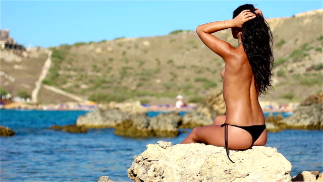 calda ragazza in topless godendo su rocce in riva al mare - persona attraente video stock e b–roll