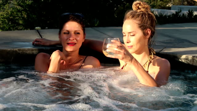 hot tub girls, sharing some wine - one piece swimsuit stock videos and b-roll footage