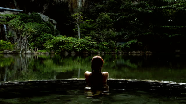 hot tub in the jungle. woman relaxing in spa retreat - vasca da bagno video stock e b–roll