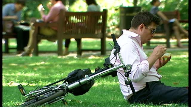 london ext barechested man lying on grass in park sunbathing / woman eating yoghurt / sunbather lying on grass / man sitting on grass next to bicycle... - bikini top stock videos & royalty-free footage