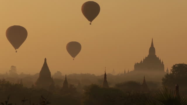 WS Hot-air balloons flying over temple at sunrise / Bagan, Myanmar