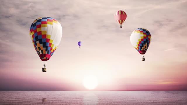 vídeos de stock e filmes b-roll de hot-air balloons flying over the sea - quatro objetos