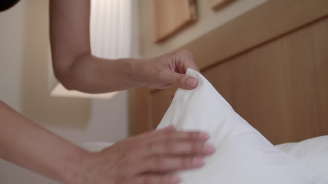 hotel chambermaid does the beding and pillows with lots of care, passion and diligence for perfect service and perfection - pillow stock videos and b-roll footage