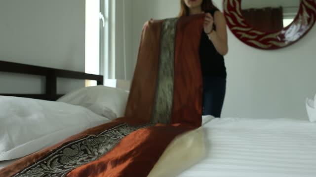 vídeos de stock e filmes b-roll de hotel chambermaid making guest bed - empreendimento turístico