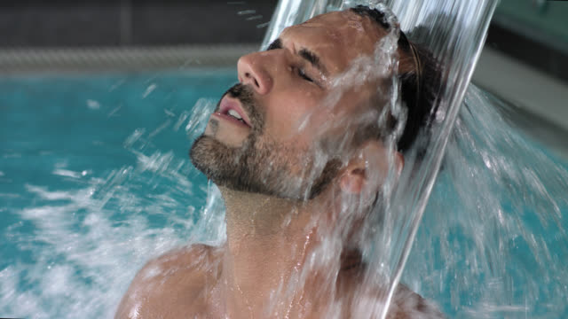 hotel day spa indoor pool with thermal spring water torrent shower – attractive sporty masculinity tanned sexy man in his 30s with short dark hair and trimmed black beard enjoying the massaging splashing foaming waters after sauna and treatments - manhood - masculinity stock videos & royalty-free footage