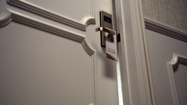 """hotel door being shut with """"do not disturb"""" sign, low angle - hotel stock videos & royalty-free footage"""