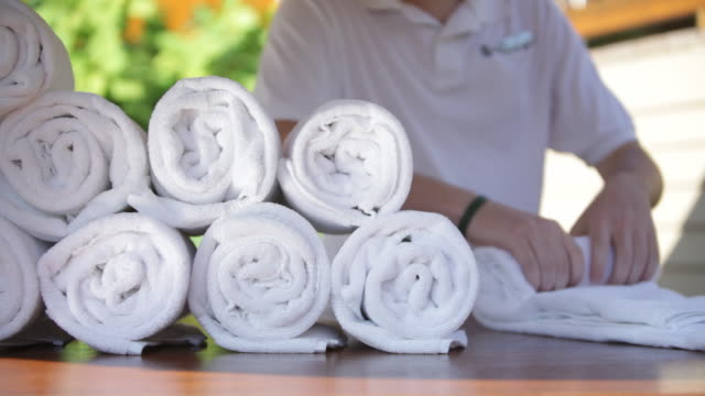 pan hotel employee rolling clean towels in outdoor cabana / stowe, vermont, united states - タオル点の映像素材/bロール