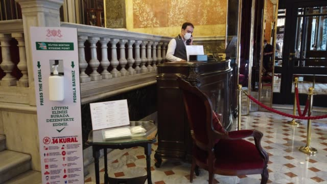 vidéos et rushes de hotel employee works at the reception desk of istanbul's historic pera palace hotel on july 04, 2020 in istanbul, turkey. after being closed for more... - museum