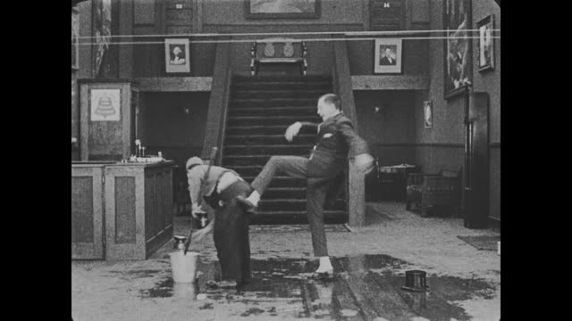 vidéos et rushes de 1918 hotel guest has his hat repeatedly knocked off of his head as the hotel's pulley system knocks it off / a fight with bellhop (buster keaton) and a waiter ensues - donner un coup de pied