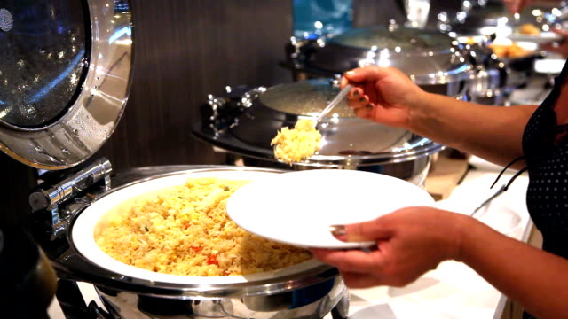 hotel guest scoop fried rice from breakfast tray food bar - food bar stock videos and b-roll footage