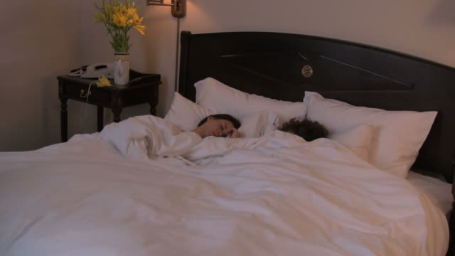 hd: hotel humor: maid makes bed on top of couple - young couple stock videos & royalty-free footage